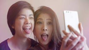 Le selfie parlant de deux femmes asiatiques photogènes heureuses avec le téléphone Images stock