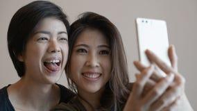 Le selfie parlant de deux femmes asiatiques photogènes heureuses avec le téléphone Image stock