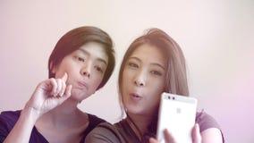 Le selfie parlant de deux femmes asiatiques photogènes heureuses avec le téléphone Photographie stock