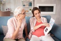 le sentiment aux cheveux foncés de femme enceinte s'est inquiété regardant les résultats médicaux Images stock