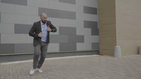 Le sentiment enthousiaste d'homme des employés a autorisé la danse l'en public près de son lieu de travail montrant des mouvement clips vidéos