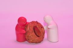 Le sentiment rouge et blanc de poupée en céramique donnent mon biscuit dans le rose Image libre de droits