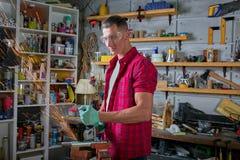 Le serrurier coupe le métal avec une machine de meulage, mécanicien que la puissance a vu des coupes image stock