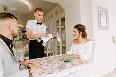 Le serveur a apporté la tasse de café pour de beaux couples dans un café Photos libres de droits