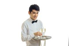 Le serveur mignon de sourire tenant un plateau et prend une main qu'un verre de champagne est isolé sur un fond blanc Image stock
