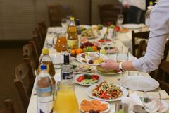 Le serveur porte des plats au festival image stock