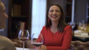 Le serveur versant le vin rouge dans le verre de la fille dans le restaurant, dame sourit Deux amies positives s'asseyant dedans clips vidéos