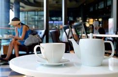 Le service à thé blanc de porcelaine a servi sur la table ronde du café image stock