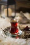 Le service à thé dans le style oriental en verre en forme de poire avec la bouilloire de vintage et les dates portent des fruits Photos stock