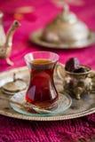 Le service à thé dans le style oriental en verre en forme de poire avec la bouilloire de vintage et les dates portent des fruits Image stock