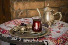 Le service à thé dans le style oriental en verre en forme de poire avec la bouilloire de vintage et les dates portent des fruits Photographie stock libre de droits