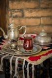 Le service à thé dans le style oriental en verre en forme de poire avec la bouilloire de vintage et les dates portent des fruits Photographie stock