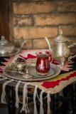 Le service à thé dans le style oriental en verre en forme de poire avec la bouilloire de vintage et les dates portent des fruits Photo stock