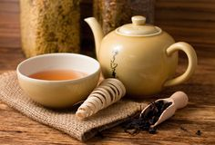 Le service à thé sur le conseil en bois et la cuillère avec le thé sec pousse des feuilles Image stock