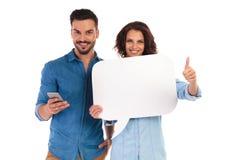 Le service de mini-messages d'homme sur le téléphone et la femme fait le signe correct Photographie stock