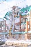 Le service de nettoyage nettoie la neige du toit de la maison image libre de droits