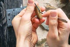 Le service principal, le serrurier ou le cambrioleur utilise un outil de serrure-cueillette pour ouvrir une porte en bois Seuleme photographie stock libre de droits