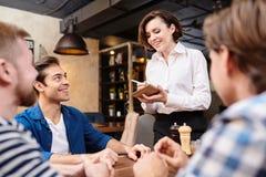 Le servitrins som gör anmärkningar, medan ta beställning royaltyfria foton