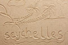 Le Seychelles scritte a mano dalla sabbia Immagini Stock