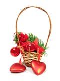 Le sfere ed i cuori rossi di natale sull'pelliccia-alberi si ramificano in cestino o Immagini Stock