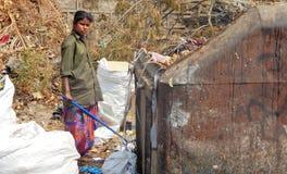 Le sfilacciatrici per stracci indiane cercano materiale riciclabile nel centro della raccolta dei rifiuti sopra Immagini Stock Libere da Diritti