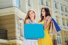 Le shopaholics d'amies se réjouissent Deux amies tenant des achats Photographie stock libre de droits