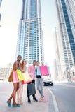 Le shopaholics gai d'amis vont au magasin pour des remises quatre Image libre de droits