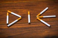 Le sigarette che si trovano sulla superficie di legno hanno modellato nella parola muoiono, concetto contro il fumo artistico Fotografie Stock Libere da Diritti