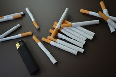 Le sigarette hanno sparso su un fondo opaco marrone con un accendino opaco nero immagine stock libera da diritti