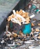 Le sigarette si intromettono possono portacenere Fotografia Stock