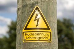 Le signe à haute tension allemand a monté sur le poteau en bois avec les arbres verts à l'arrière-plan image stock
