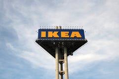 Le signe élevé de triangle de couleur jaune et bleue IKEA devant IKEA stockent Photos libres de droits