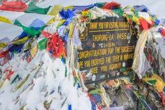 Le signe avec les drapeaux bouddhistes de prière à la montagne de La de Thorong au Népal Images stock
