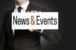 Le signe d'actualités et d'événements est tenu par l'homme d'affaires Images libres de droits