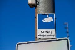 Le signe d'appareil-photo de surveillance accroche sur un poteau de lampe Photo stock