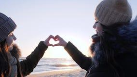 Le signe de l'amour, les femmes homosexuelles de couples fait le coeur avec des mains au coucher du soleil banque de vidéos