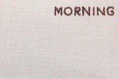Le signe de lettre de matin des grains de café d'isolement sur la texture de linea, a aligné en haut à droite photographie stock