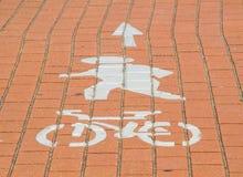 Le signe de piéton et de chemin de cycle a peint sur la surface de brique rouge images libres de droits