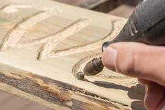 Le signe en bois créatif est fait avec une fraiseuse images stock