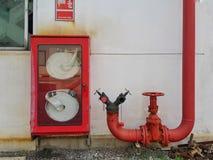Le signe et le tuyau de bobine de tuyau d'incendie tournoient dans la boîte photographie stock libre de droits