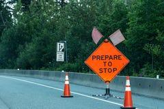 Le signe orange lumineux qui lit soit préparé pour s'arrêter avertit une ligne des automobilistes de la construction de routes en images libres de droits