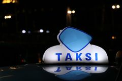 Le signe ou la cabine de lumi?re de taxi signent dans la couleur bleue et blanche sur le toit de voiture ? la rue pendant la nuit image stock