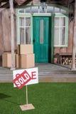 Le signe s'est vendu sur l'herbe verte et les boîtes en carton empilant sur le porche Photographie stock libre de droits