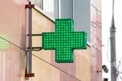 Le signe urbain de pharmacie ou de pharmacie, a mené la croix verte d'affichage sur le mur dans la rue de ville photos stock