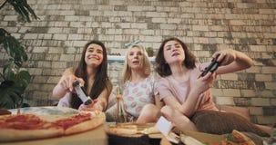 Le signore carismatiche in pigiami si divertono che gioca insieme su un primo piano di PlayStation davanti alla macchina fotograf archivi video