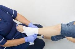 Le signore hanno ferito la caviglia che è vestita da un infermiere Immagini Stock