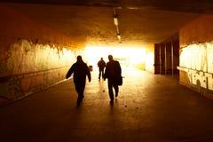 Le siluette che camminano in un lerciume urbano scavano una galleria Fotografia Stock Libera da Diritti