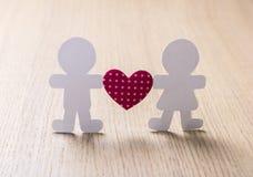 Le siluette degli uomini, delle donne e del cuore hanno tagliato di carta Immagini Stock
