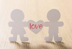 Le siluette degli uomini, delle donne e del cuore hanno tagliato di carta Immagine Stock