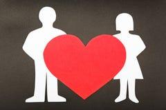 Le siluette degli uomini, delle donne e del cuore hanno tagliato di pape. Fotografia Stock